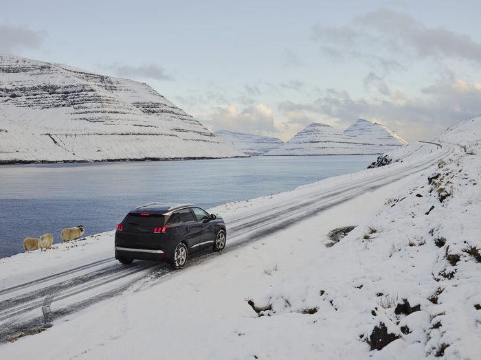 Car on snowcapped mountain against sky