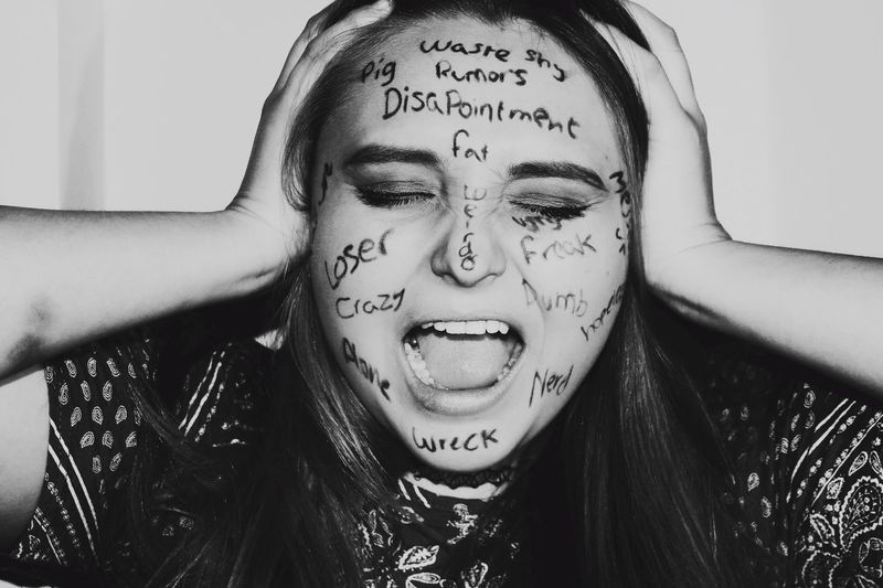 Young woman with text on face screaming at home