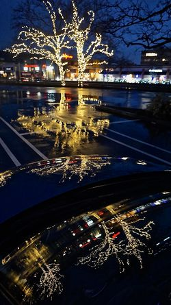 Car Holiday Lighting Illuminated Parking Lot Pavement Rain Reflections In Water Tree