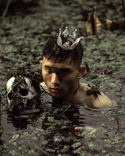 Man wearing crown while swimming in lake