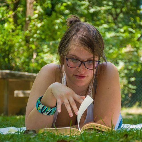 Portrait of young woman sitting on grass and read a book