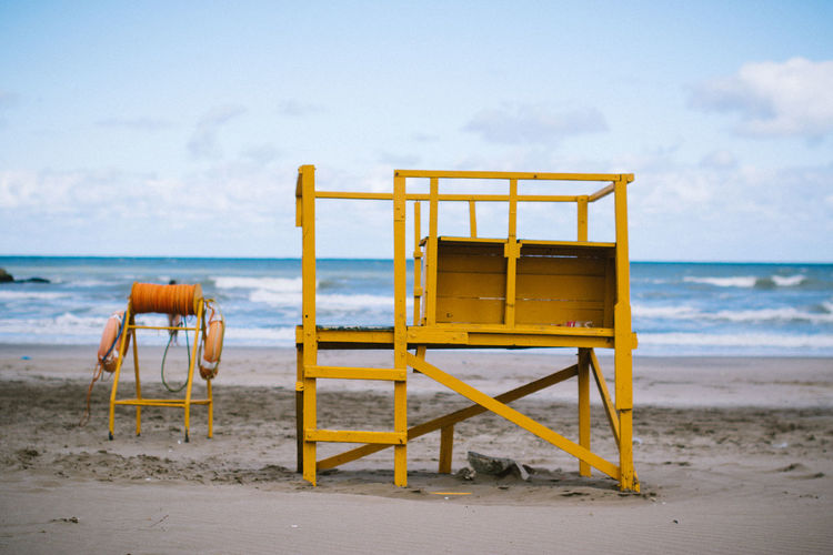 Lifeguard chair on sand at beach against sky