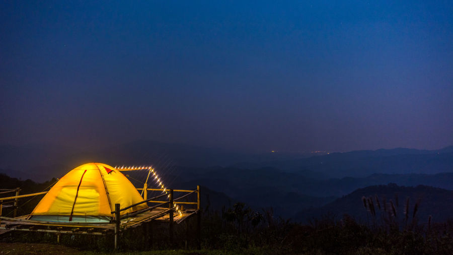Doi Kad Phee in Chiang Rai in northern Thailand. Chiang Rai, Thailand Doi Kad Phee Adventure Beauty In Nature Camping Clear Sky Doi Illuminated Landscape Mountain Mountain Range Nature Night No People Outdoors Scenics Sky Sunset Tent Tranquility Vacations Yellow