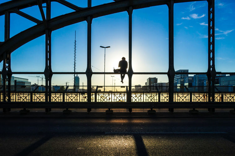 Silhouette man sitting on bridge against sky during sunset