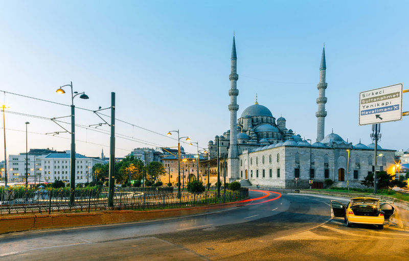 Light trails on road against historic mosque in city