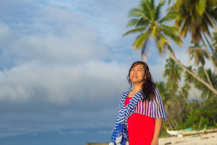 Woman standing by palm tree against sky