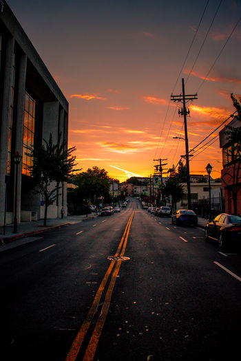 Sunset Ave. Architecture Building Exterior Built Structure Car City Diminishing Perspective Direction Land Vehicle Mode Of Transportation Motor Vehicle Nature No People Orange Color Road Sign Sky Street Sunset The Way Forward Transportation