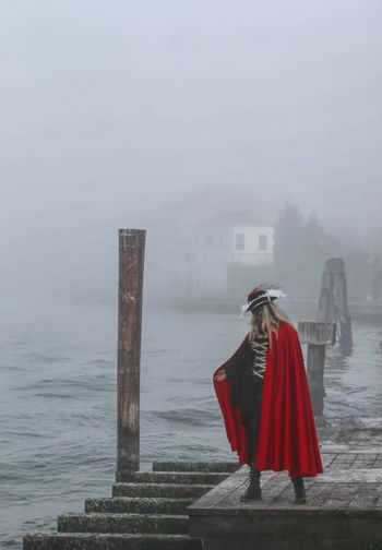 Woman in costume standing on pier during extreme weather