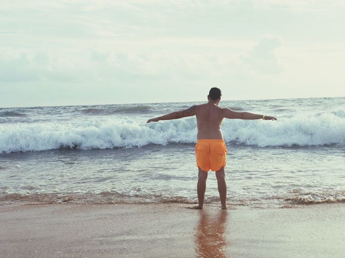 Rear View Of Shirtless Man With Arms Outstretched Standing At Beach
