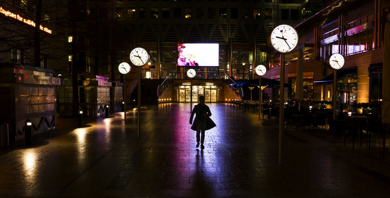 illuminated, walking, real people, night, rear view, built structure, clock, full length, architecture, women, lifestyles, one person, men, time, indoors, people