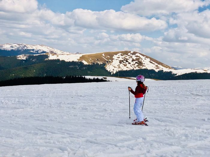 Woman on skiing on snow covered field against sky
