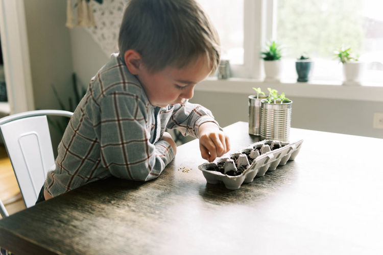 Rear view of boy playing with table at home