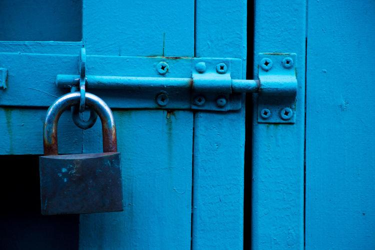 Close-Up Of Padlock On Blue Door