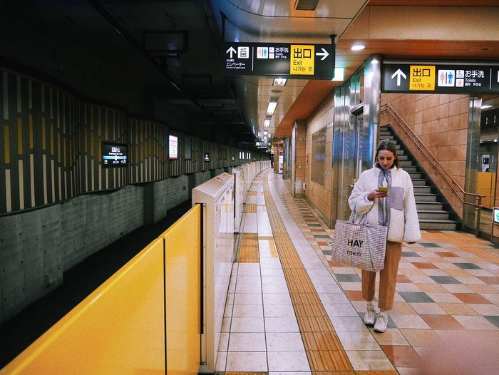 Full length of man walking in illuminated underground walkway