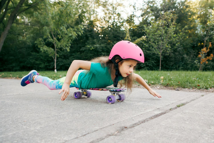 Happy smiling caucasian girl in pink helmet lying on tummy riding skateboard on road in park
