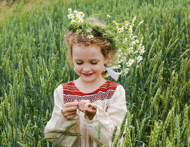 Smiling Girl Wearing Flowers Standing On Field