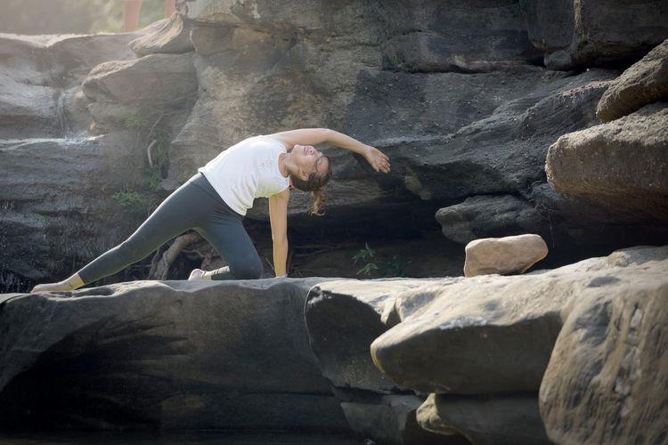 Full Length Of Woman Doing Yoga On Rock