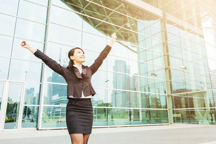 Confident Young Businesswoman Standing With Clenched Fist Against Office Building