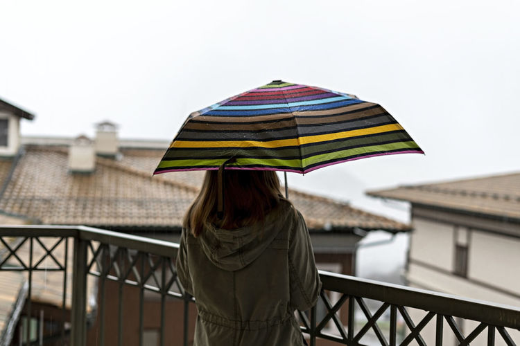 Young woman from behind with umbrella in rainbow pattern in drops standing on terrace in rain