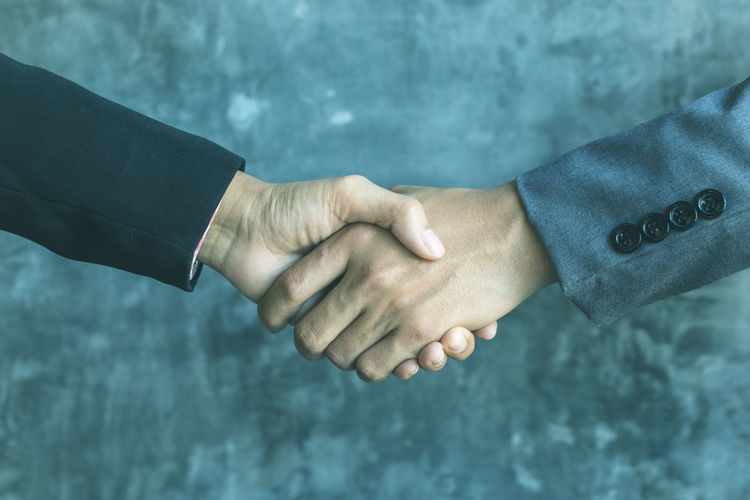 Cropped hands of businessmen shaking hands against wall