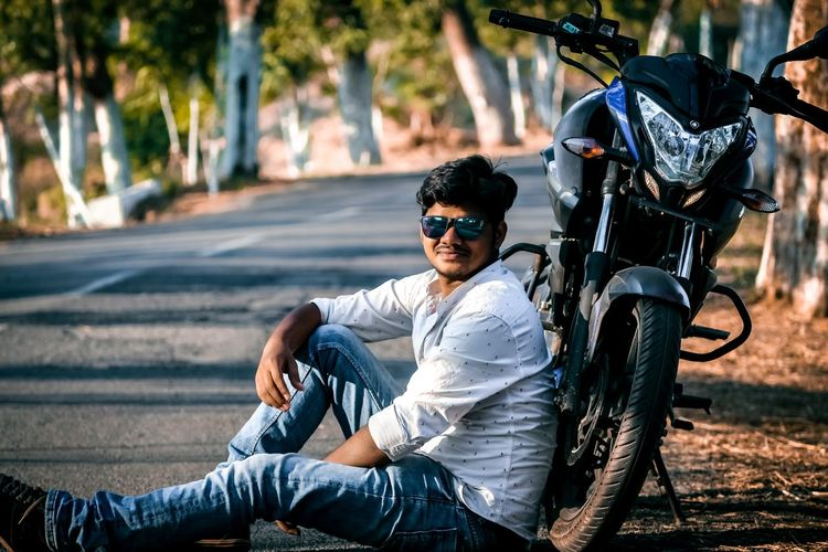 Portrait of young man wearing sunglasses while sitting by motorcycle on road