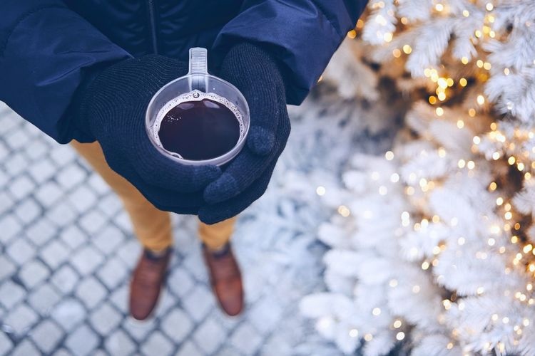 Low Section Of Man Holding Black Coffee While Standing By Illuminated Christmas Tree During Winter