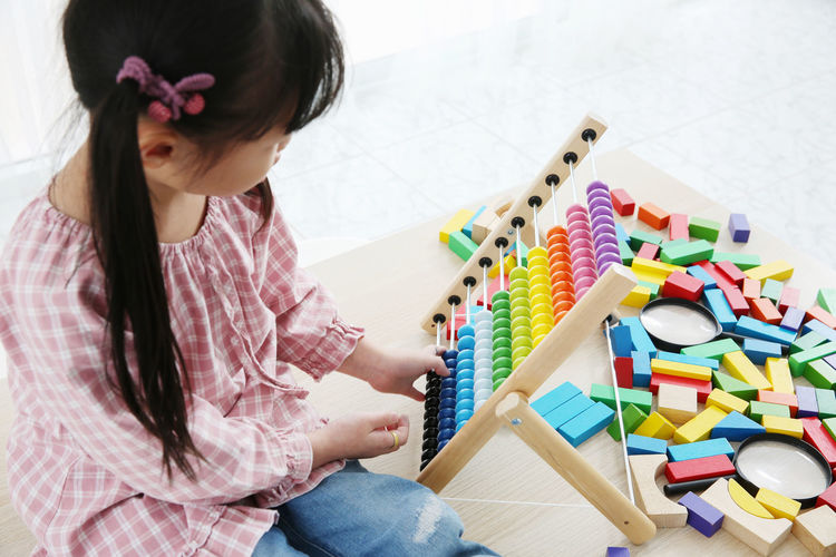 Girl playing with abacus on table
