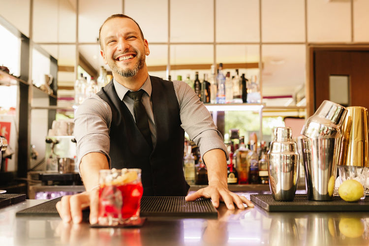 Happy Bartender Serving Drink At Counter