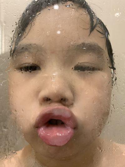 Close-up portrait of wet girl in bathroom