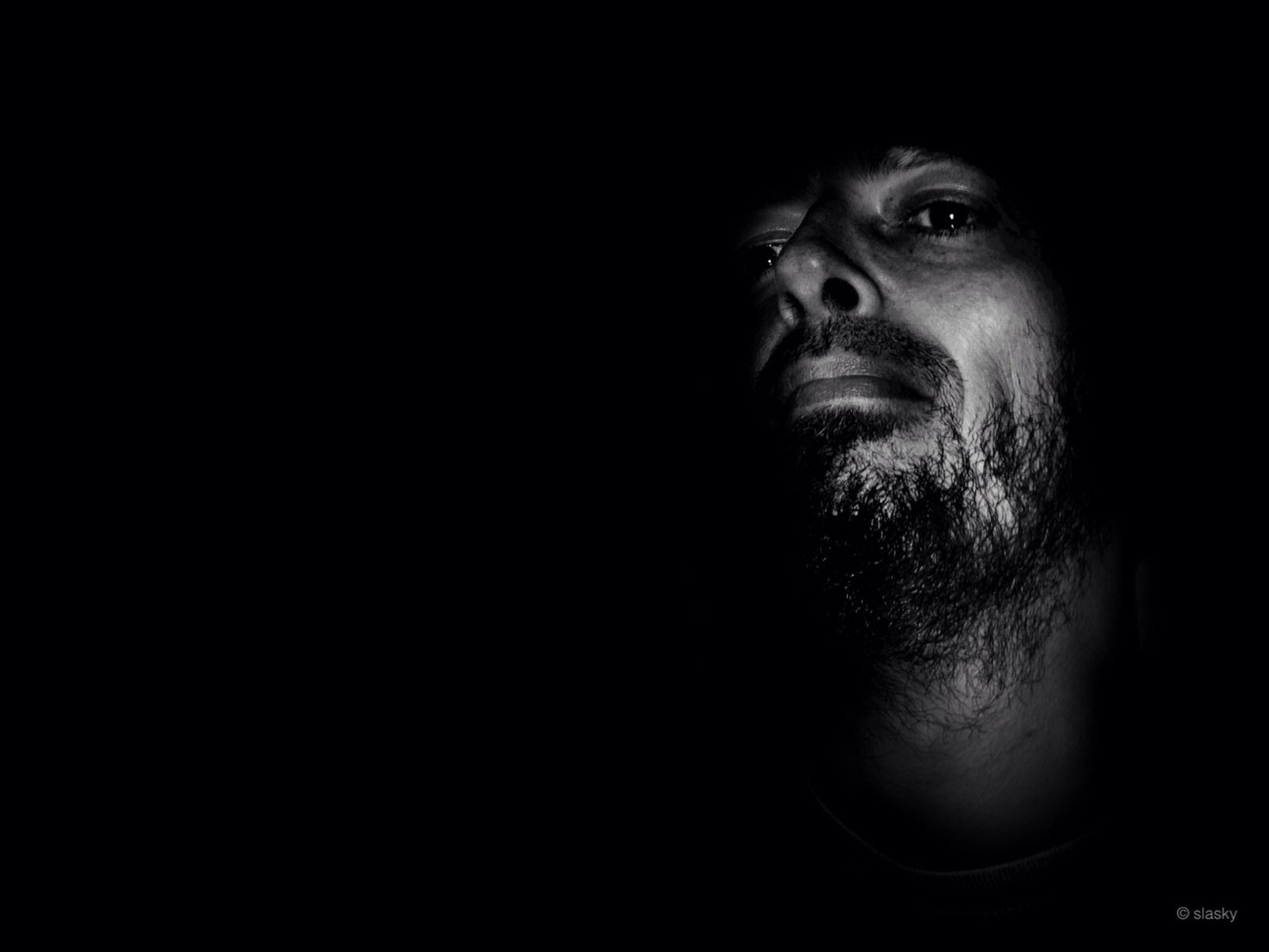 black background, studio shot, headshot, young adult, copy space, portrait, looking at camera, lifestyles, person, human face, indoors, close-up, front view, dark, contemplation, serious, young men