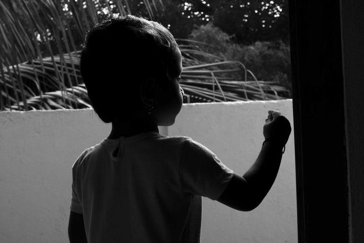 Rear view of girl standing at door