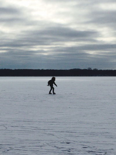 Silhouette person in sea against sky during winter
