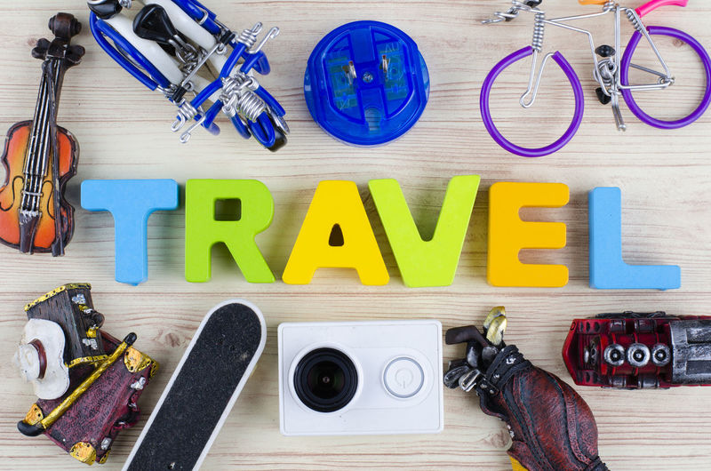 top view vacation and holiday concept word TRAVEL with accessories on wooden background Indoors  Directly Above Still Life Table Large Group Of Objects High Angle View No People Multi Colored Wood - Material Text Equipment Choice Variation Work Tool Scissors Capital Letter Western Script Tool Hand Tool Hand Saw