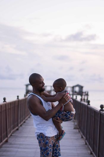 Father Carrying Son While Standing On Pier Against Sky During Sunset