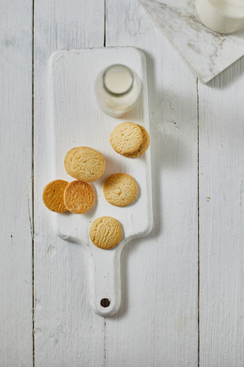 Directly above shot of cookies by milk in bottle on table