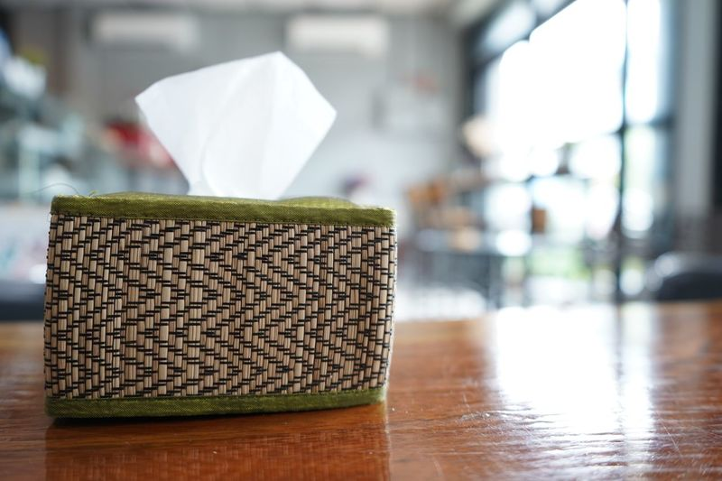Close-up of paper tissue container on table at restaurant