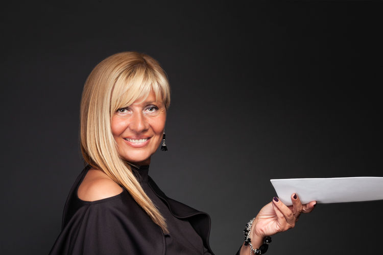 Close-Up Portrait Of Happy Woman Holding Paper While Standing Against Black Background