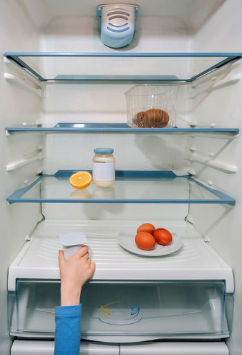 Cropped hand holding food in refrigerator