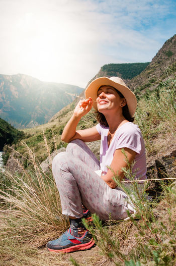 Adult Beauty In Nature Casual Clothing Day Full Length Happiness Hat Landscape Leisure Activity Lifestyles Mountain Mountain Range Nature One Person Outdoors Plant Scenics - Nature Sitting Smiling Young Adult