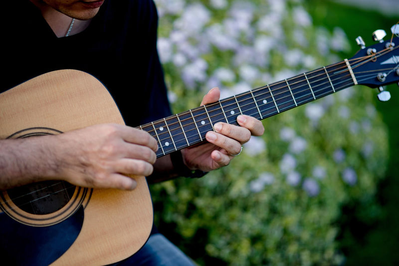 Midsection of man playing guitar while sitting outdoors