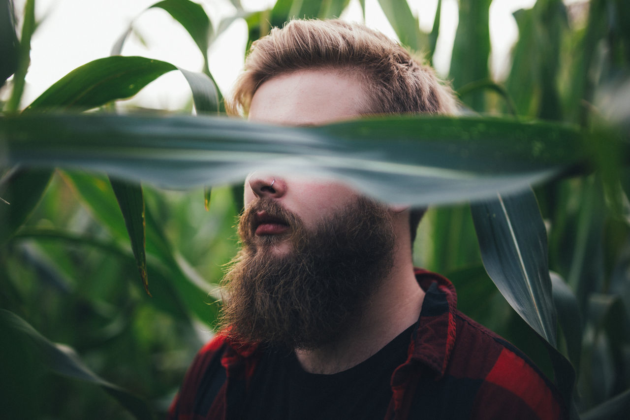 CLOSE-UP OF YOUNG MAN WITH PLANTS