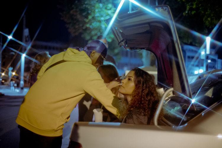 People in illuminated car at night