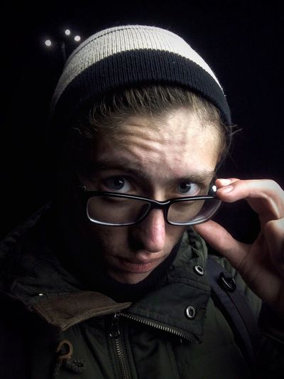 Close-up portrait of man wearing eyeglasses against black background