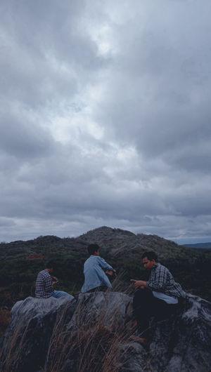 People sitting on rock against sky