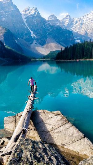 Man walking on fallen tree over lake against mountains
