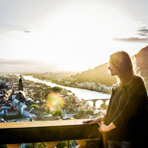 Side view of smiling woman looking at city from balcony