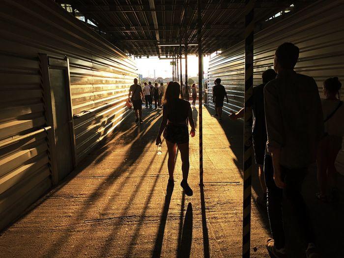 Rear view of people walking on railway station
