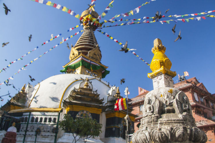 Low angle view of praying flags on temple against clear blue sky