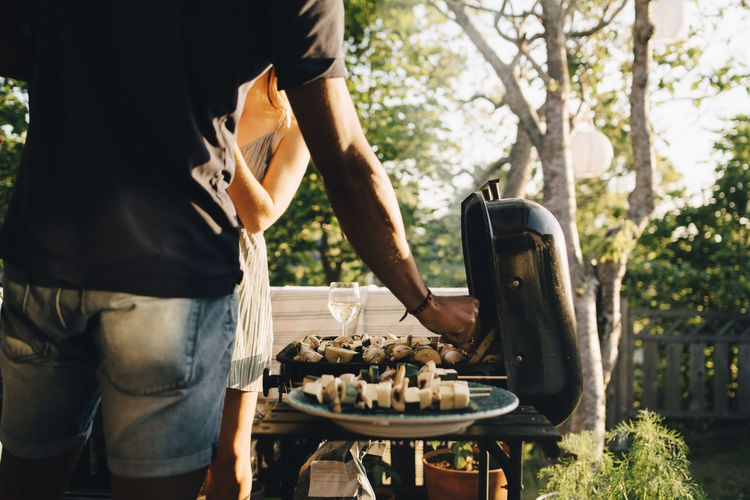 Midsection of man standing on barbecue grill in yard