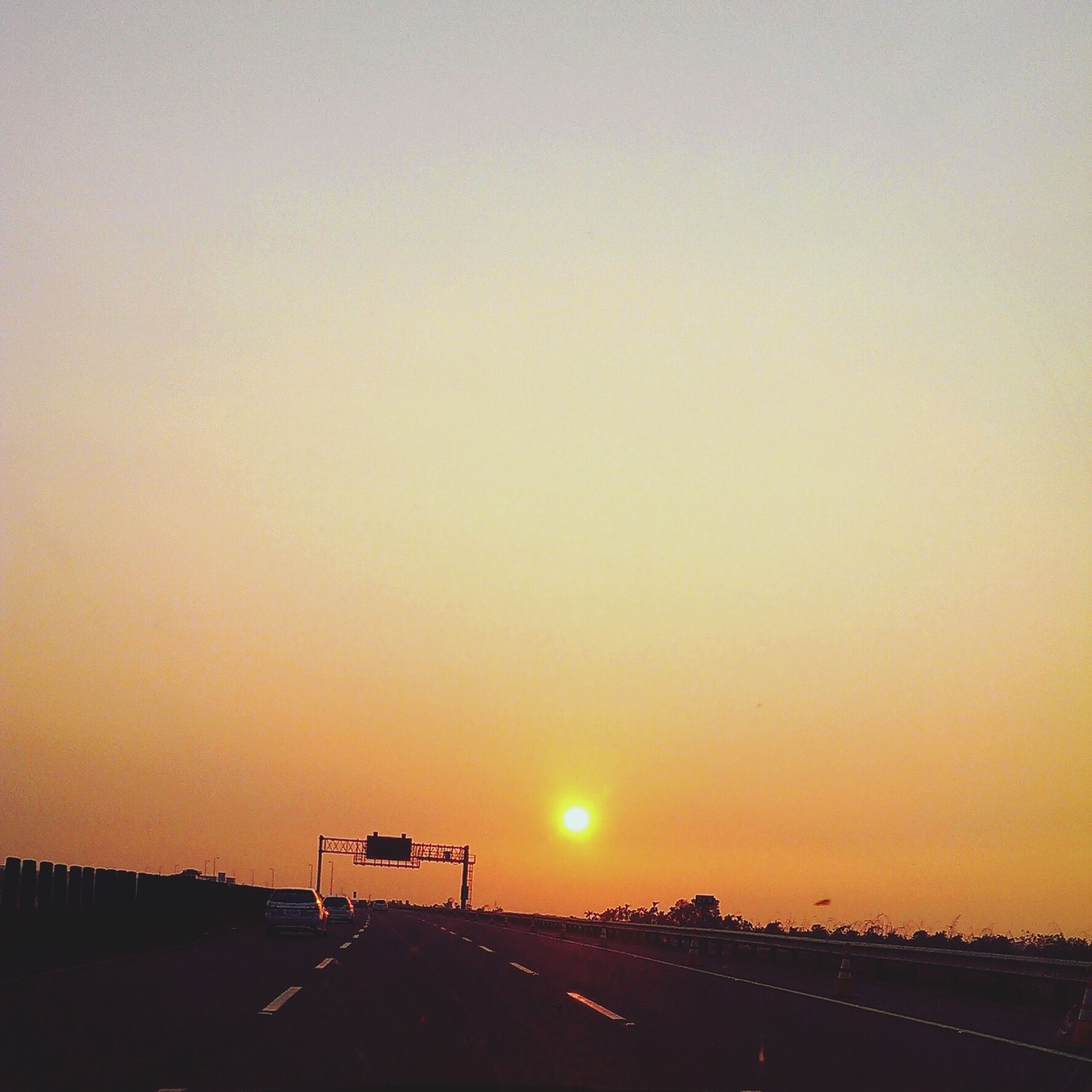 sunset, clear sky, copy space, orange color, sun, silhouette, sunlight, scenics, built structure, tranquility, landscape, tranquil scene, beauty in nature, nature, architecture, road, transportation, outdoors, no people, idyllic